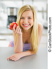 Portrait of smiling young woman with apple