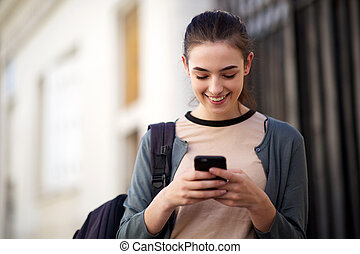 smiling young woman with bag looking at cellphone
