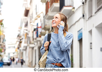 smiling young woman with cellphone in the city