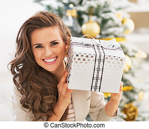 Portrait of smiling young woman with christmas present box