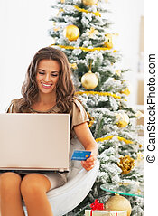 Portrait of smiling young woman with credit card using laptop near christmas tree