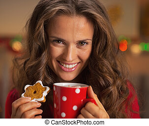 Portrait of smiling young woman with cup of hot chocolate and christmas cookie