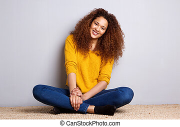 smiling young woman with curly hair sitting on floor