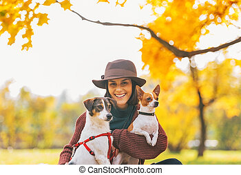 Portrait of smiling young woman with dogs outdoors in autumn