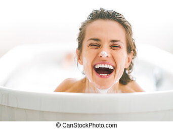 Portrait of smiling young woman with foam on face looking out fr