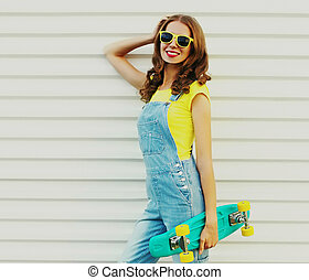 Portrait of smiling young woman with green skateboard on a white background