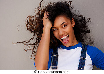 smiling young woman with hand in hair against gray background