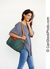 smiling young woman with handbag making a phone call
