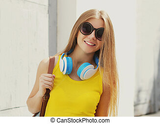 Portrait of smiling young woman with headphones listening to music on in the city