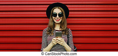 Portrait of smiling young woman with phone on a red background
