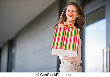 Portrait of smiling young woman with shopping bag looking on cop