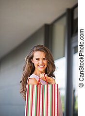 Portrait of smiling young woman with shopping bag