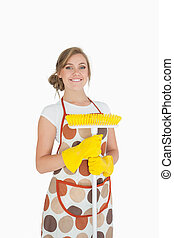 Portrait of smiling young woman with broom