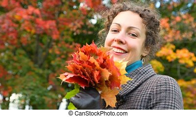 portrait of smiling young woman with autumn leaves in park