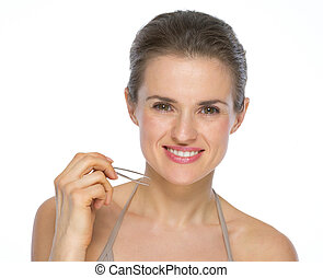 Portrait of smiling young woman with tweezers