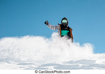 Portrait of snowboarder in sportswear riding down the powder snow hill