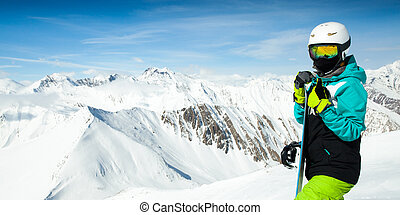 Portrait of snowboarder woman on background landscape of snowy high mountains