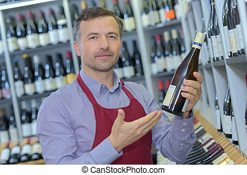 portrait of sommelier with wine bottle in wine shop
