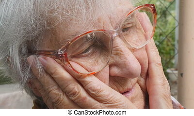 Portrait of sorrowful grandmother with emotions and feelings. old woman looking with sad expression outdoor. Grandma keeping hands at her face and sighing heavily. Close up Side view Slow motion