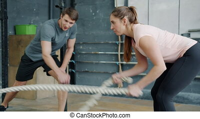 Portrait of young attractive sportswoman exercising with battle ropes in gym with support of crossfit trainer handsome guy in sportswear. People and sports concept.