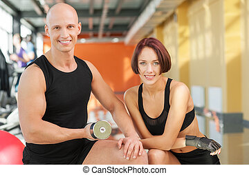 Portrait of sporty couple with dumbbells smiling at camera