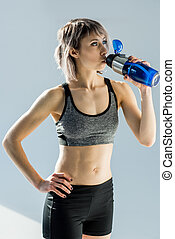 sporty woman drinking water from bottle after training