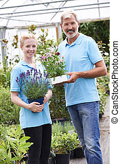 Portrait Of Staff At Garden Center Holding Plants
