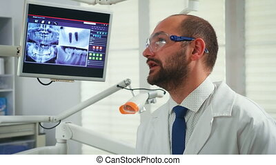 Portrait of stomatologist telling the treatment to elderly woman having digital x-ray in background. Doctor working in modern stomatological office explaining radiography of teeth from digital monitor