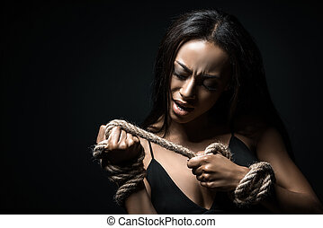 portrait of stressed african american woman bound with rope isolated on black