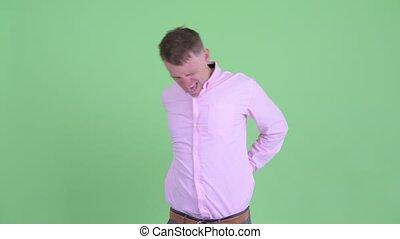 Portrait of stressed businessman having back pain
