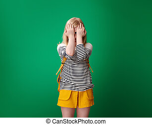 Portrait of stressed pupil with backpack isolated on green