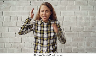 Portrait of stressed young woman screaming and gesturing...