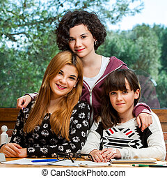 Portrait of student threesome at desk. - Family portrait of...