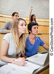 Portrait of students listening a lecturer while their classmate is raising her hand in an amphitheater