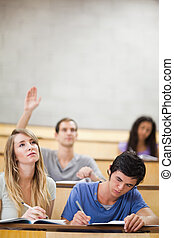 Portrait of students taking notes while their classmate is raising his hand in an amphitheater