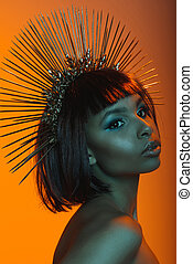 portrait of stylish african american woman posing in headpiece with needles