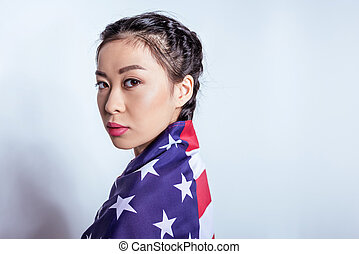 Portrait of stylish asian girl wrapped in american flag looking at camera isolated on grey