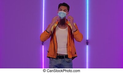 Portrait of stylish guy puts on and then removes the medical protective mask. Male fashion model in yellow jacket poses in dark studio against the backdrop of bright neon lights. Slow motion.