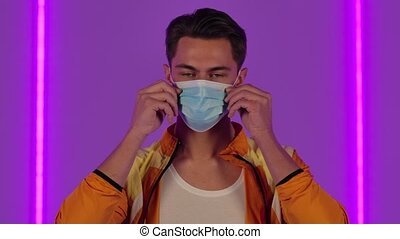 Portrait of stylish guy puts on and then removes the medical protective mask. Male fashion model in yellow jacket poses in dark studio against the backdrop of bright neon lights. Close up. Slow motion