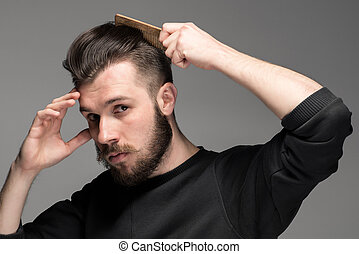 Portrait of stylish handsome young man combing his hair -...