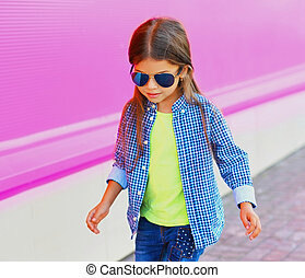 Portrait of stylish little girl child in the city over a pink background