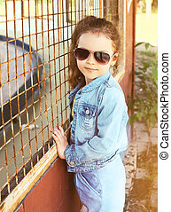 Portrait of stylish little girl child wearing a jeans clothes and sunglasses posing outdoors