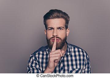 portrait of stylish man with beard show sign silence