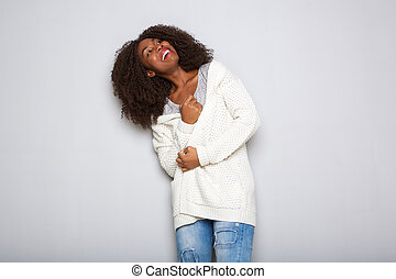 stylish young african woman in cardigan looking away on white background
