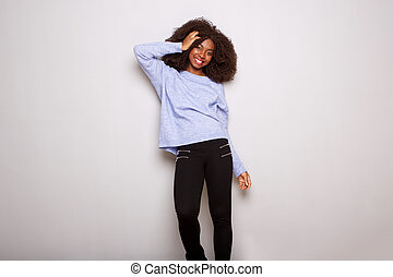 stylish young african woman standing with hand in hair on white background