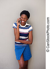 stylish young african woman talking on cell phone against gray background