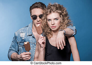 Portrait of stylish young couple in love standing embracing and holding ice cream