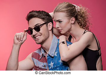 portrait of stylish young couple in love isolated on pink