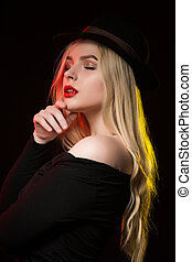 Portrait of stylish young lady in hat posing in the shadow with yellow and red light