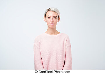 portrait of stylish young pretty woman smiling standing in pink sweater on white studio background